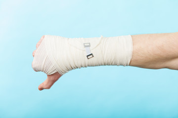 Male bandaged hand with thumb down sign.