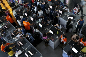 Indonesian youths fill up job application forms on laptops during the Career & Higher Education Fair in Jakarta