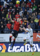 Osasuna's Fernandez and Valencia's Soldado leap for the ball during their Spanish First Division soccer match in Pamplona