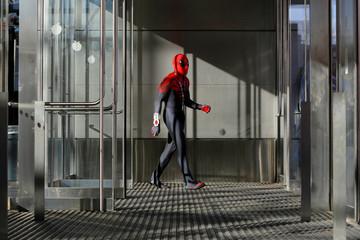 A men dressed as Spiderman walks through a doorway at New York Comic Con in Manhattan