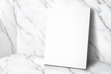 Blank white poster canvas in white glossy marble floor leaning at wall,Mock up template for display or montage of design or text,Business presentation