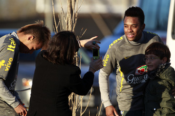 Brazilian soccer player Robinho poses for a picture with a fan, as Neymar signs his autograph, after their training session in Los Cardales