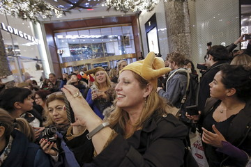 A woman in a turkey hat takes a photo as she enters Macy's Herald Square store during the early opening of the Black Friday sales in the Manhattan borough of New York