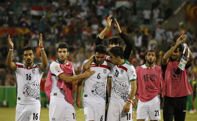 Iraq's Ali Adnan Kadhim is consoled as team mates acknowledge their fans following their defeat in the Asian Cup quarter-final soccer match between Iran and Iraq at the Canberra stadium in Canberra