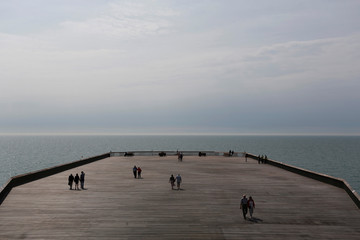 People walk on the newly re-opened pier at Hastings in southeast England