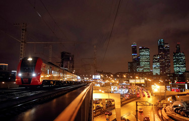 Train moves along Moscow Central Ring railway, with Moscow International Business Centre seen in background, in Moscow