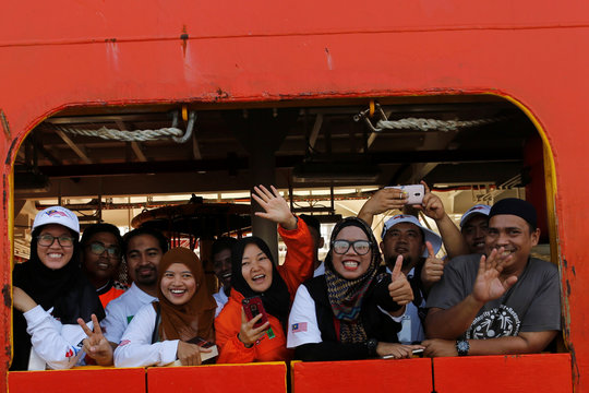 Crew of Malaysian NGO's aid ship carrying food and emergency supplies for Rohingya Muslims wave while they arrive at the port in Yangon