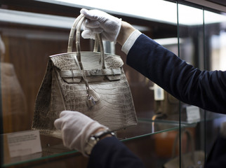 An employee places an Hermes diamond and Himalayan Nilo Crocodile Birkin handbag in a case at Heritage Auctions offices in Beverly Hills