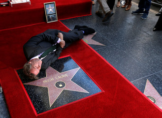 Actor Laurie poses on his star after it was unveiled on the Hollywood Walk of Fame in Los Angeles