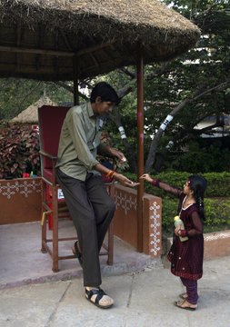 A girl gives money to Gattaiah, who claims to be the tallest man in India, at the arts and crafts centre in the southern Indian city of Hyderabad