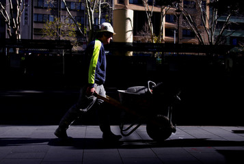 A worker pushes a wheelbarrow loaded with tools near a construction site in central Sydney, Australia