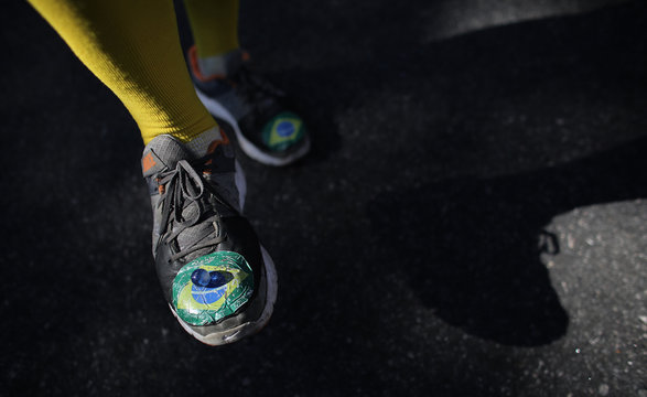 Man plays with a marble as his shoes bear the colours of the Brazilian flag at Vila Madalena neighbourhood after the 2014 World Cup round of 16 soccer match between Argentina and Switzerland in Sao Paulo