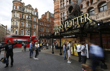 People stand outside The Palace Theatre where the Harry Potter and The Cursed Child play is being staged, in London