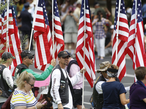Members of local motorcycle riding groups hold American flags as a motorcade of hearses carrying the remains of members of the Granite Mountain Hotshots firefighting team approaches the Wesley Bolin Memorial Plaza in Phoenix