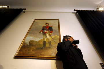 A painting of Chilean national hero Bernardo O'Higgins hangs in a room as a member of the media attends a speech by Chile's President Bachelet at the government palace in Santiago
