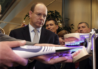 Prince Albert II of Monaco looks at a monitor as he uses a digital camera to make a dental scan during a visit to the Imagina digital imaging exhibition in Monaco