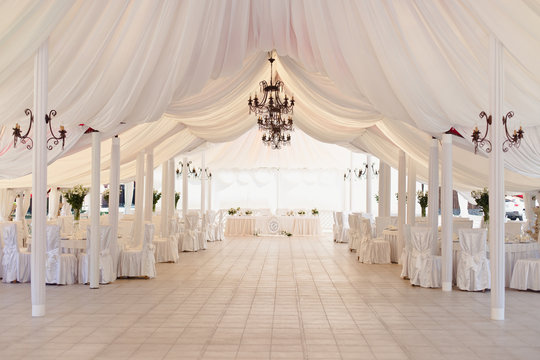 Marquee for the celebration of the wedding. Beautiful white interior with white draperies