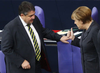 German Chancellor Merkel speaks with Economy Minister Gabriel during a session of the Bundestag, the German lower house of parliament, in Berlin