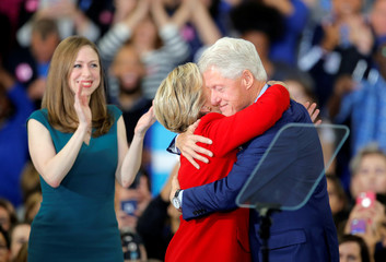Former President Bill Clinton shares a hug with her wife and democratic presidential nominee Hillary Clinton after introducing her at a campaign rally in Raleigh