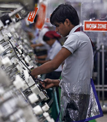 An employee works on a wiring section of a vehicle at the factory of Samvardhana Motherson Group in Noida