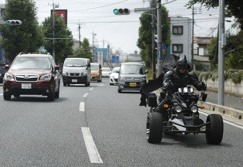 "A 41-year-old man going by the name of Chibatman rides his ""Chibatpod"" on the road in Chiba, east of Tokyo"