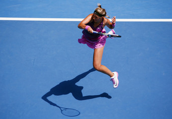 Victoria Azarenka of Belarus hits a return to Sloane Stephens of the U.S. during their women's singles match at the Australian Open 2014 tennis tournament in Melbourne