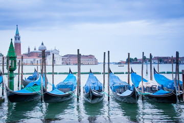 Gondolas floating on the water with Venice in the background.