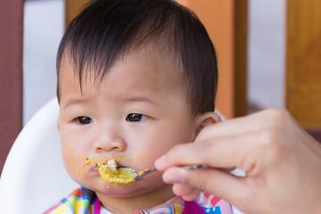 Asian cute baby boring eat food.