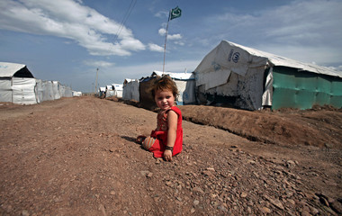 Internally displaced girl sits outside her family tent at the UNHCR Jalozai camp in Khyber-Pakhtunkhwa province