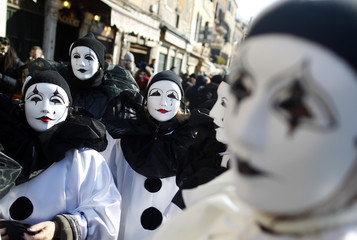 Masked revellers pose near Saint Mark's Square during the Venetian Carnival in Venice