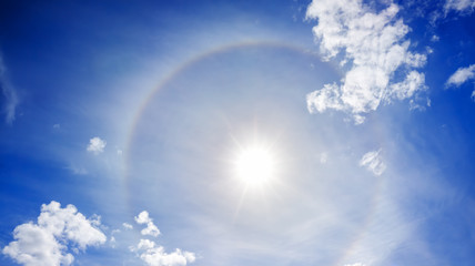 landscape from the blue sky with sun, white clouds and halo