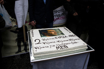 Protesting health workers stand around a cake with a picture of Greek PM Tsipras as Pinocchio, during a demonstration against government plans affecting their sector, near the PM's office in Athens