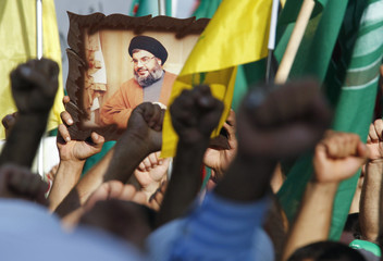 Protesters gesture as they carry Hezbollah and Amal movement flags and a picture of Lebanon's Hezbollah leader Sayyed Hassan Nasrallah at a protest against a film made in the United States that mocks the Prophet Mohammad