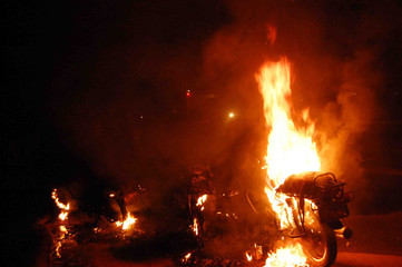Motorcycles burn at the scene of a fatal road accident that led to a fuel tanker catching fire on the outskirts of the capital Kampala
