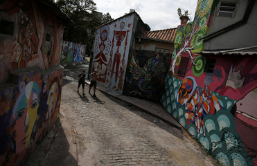 "Couple walks between graffiti-filled walls along ""Beco do Batman"" (Batman's alley) in the Vila Madalena neighbourhood, which is a well-known open-air graffiti museum, in Sao Paulo"