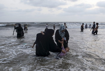 A boy is held by his mother as he slips in the Arabian Sea at a beach on a hot summer day in Mumbai