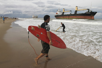 Surfers enter the water next to two cargo ships which lie stranded close to the shore in Valencia after a heavy rainstorm in Valencia