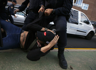 A demonstrator is pushed by a Spanish riot police officer as a veterinarian van, apparently carrying Excalibur, the dog of the Spanish nurse who contracted Ebola, leaves from her apartment complex in Alcorcon