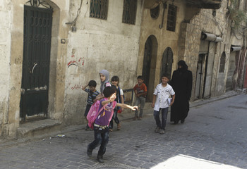 A woman walks with schoolchildren along a street in the old city of Aleppo