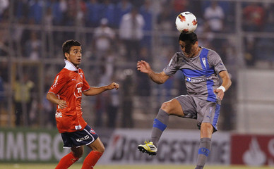 Gazale of Universidad Catolica jumps for the ball next to Fredes of Independiente during their Copa Sudamericana soccer match in Santiago