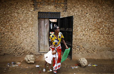 A woman holding her child walks out of her house at Mishomoroni area of Kenya's coastal city of Mombasa