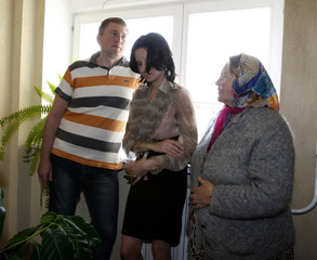 Uss stands with his wife Evgeniya and mother Sofia in a court building before hearings in Minsk