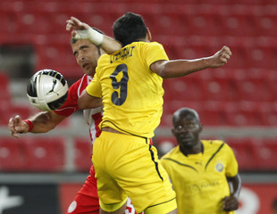 Olympiakos' Maresca fights for the ball against Maccabi Tel-Aviv's Itzaki during their third qualifying round Europa League soccer match in Athens