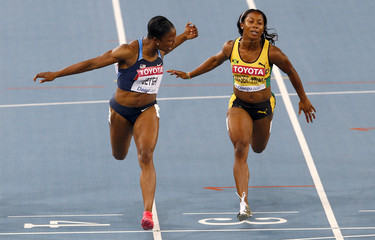 Carmelita Jeter of the U.S. lunges at the finish line ahead of Shelly-Ann Fraser-Pryce of Jamaica winning the women's 100 metres final in Daegu