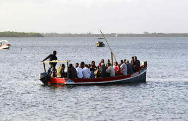 Kenyan travel on a boat near the beach home of a disabled French woman held hostage in Ras-Kitau on Manda Island in Lamu