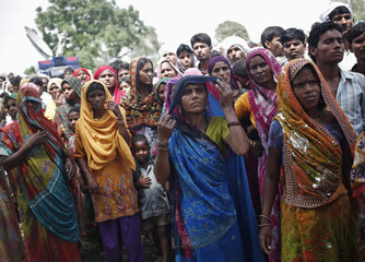 Onlookers stand at the site where two teenage girls, who were raped, were hanged from a tree at Budaun district in the northern Indian state of Uttar Pradesh
