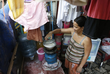 Nancy Bolata cooks rice at home in a squatter colony in Quezon city, Manila