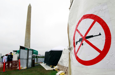 """A """"No Weapons"""" sign is seen at a refugee camp exhibit in Washington"""