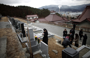 A woman prays in front of a relative's grave, who was killed during last year's earthquake and tsunami, in Ofunato, Iwate Prefecture