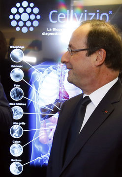 French President Hollande looks on during the presentation of Cellvizio, a Medical Endomicroscopy virtual assistant at Mauna Kea Technologies office in Paris